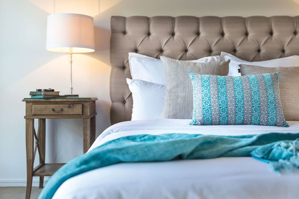 Bed with pillows, cushions and throw rugs in an apartment at Strathalan Macleod