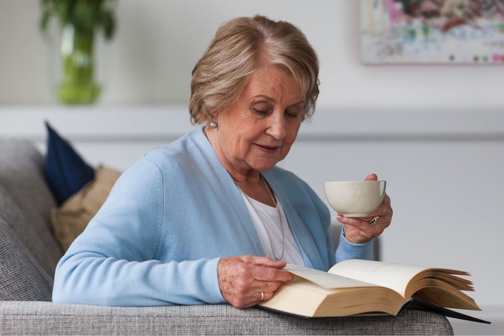 Senior woman reading a book, drinking tea at Strathalan Macleod