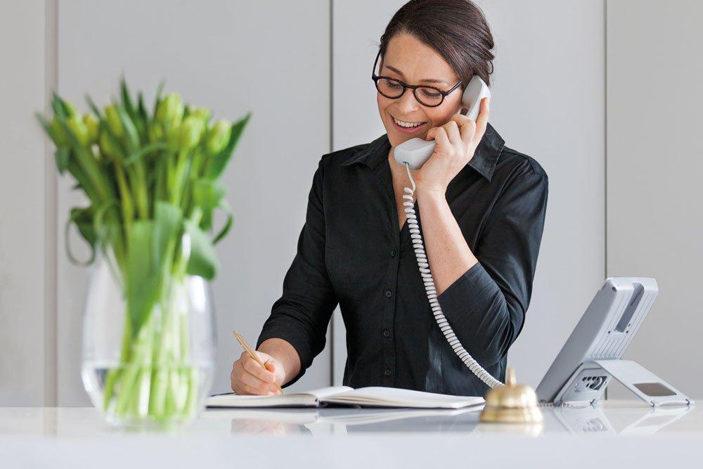 Woman on a telephone at reception at Strathalan Macleod