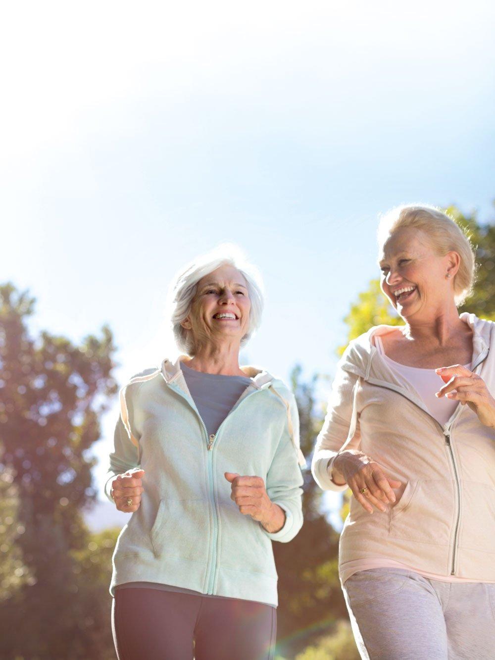 Two senior women running together outside, smiling, sun shining at Strathalan Macleod